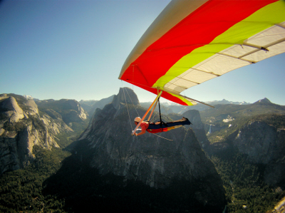 A yellow, red and white hang glider passes over the beautiful mountain terrain in the background.