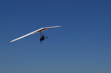 An individual hang glides in clear blue skies with Kite Enterprises Hang Gliding and Paragliding in Allen, Texas.