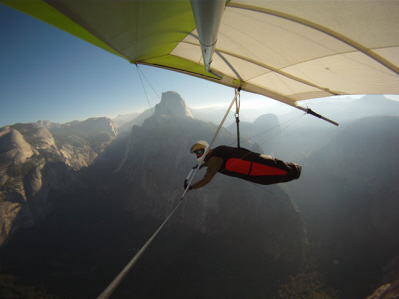 A white hang glider with yellow outline flies above a mountainous terrain.