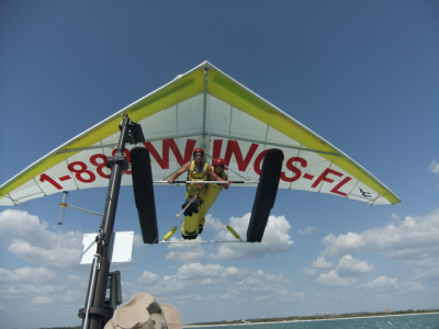 A closeup of tandem hang gliders. The hang glider is white with yellow outline. A phone number in large red letters stretches across the glider and reads 1-888-WINGS-Florida.