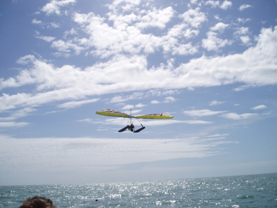 A yellow and white hang glider flies over the ocean water in the clear sky with thin clouds.