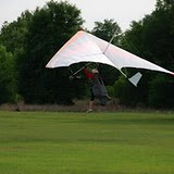 A white hang glider takes off in a green field