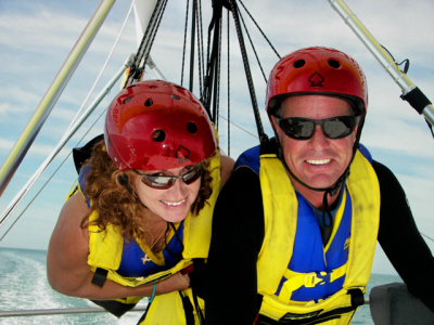 A closeup of a man and a woman hang gliding. They are both wearing red helmets and yellow vests. The clear Florida water is the background.