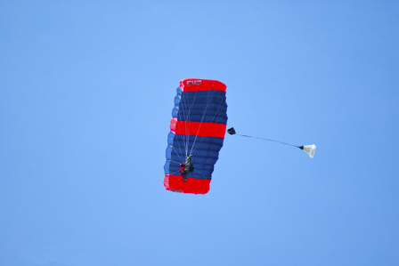 A jumper flies under their red and blue parachute after a BASE jump