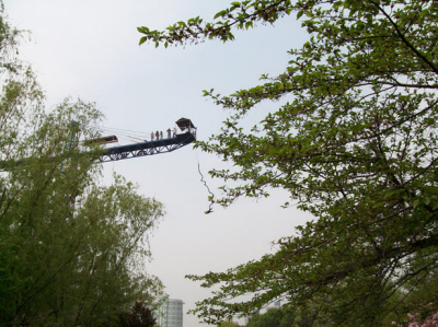 Bungee Jumping: A bungee jumper is falling toward the ground after jumping from a crane. Five spectators or instructors stand along the crane beam.