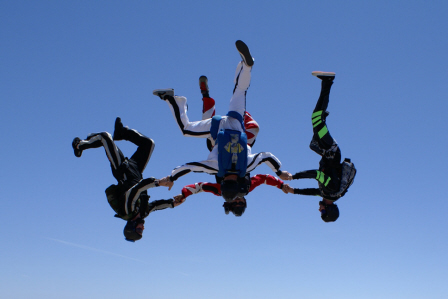Four skydivers at Skydive Taft fly head first toward the ground in a circular formation while holding hands