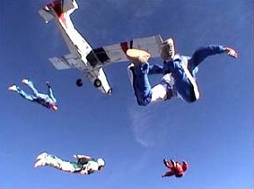 Four skydivers at Skydive Phoenix fall toward earth with the plane in the background