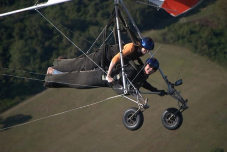 Quest Air Hang Gliding - Two people fly a hang glider over green open terrain.