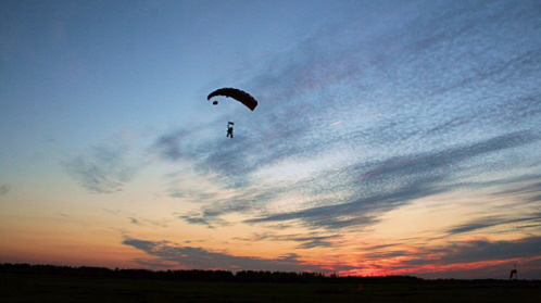 No Limits Skydiving - A skydiver navigates to land in dusk