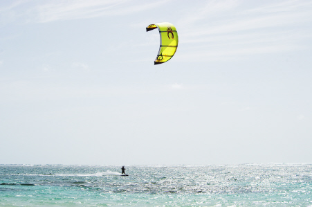 A surfer surfs across crystal blue water with a yellow kite.