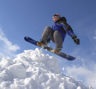 A snowboarder gets some air as they fly over a large pile of snow.