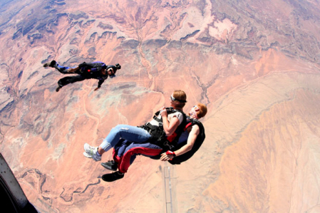 Skydive Moab - A skydiver with a helmet camera falls below a pair of tandem skydivers above the desert below