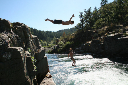 A man and a woman jump from a cliff into a lake.
