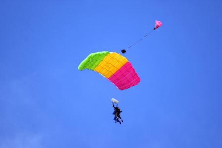 Tandem skydivers fly under a green, yellow and pink canopy in the clear blue sky