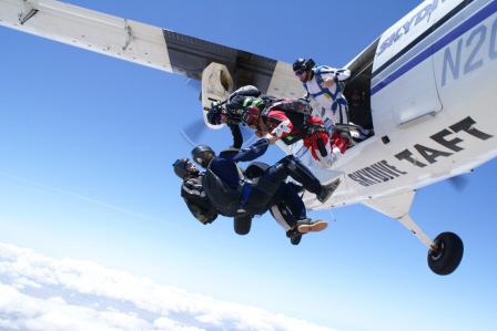Five people jumping from an airplane at Skydive Taft