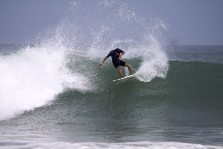Learn How to Surf - A surfer in a wet suit rides a wave.
