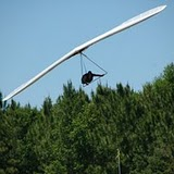 A hang glider flies low with green trees in the backgound