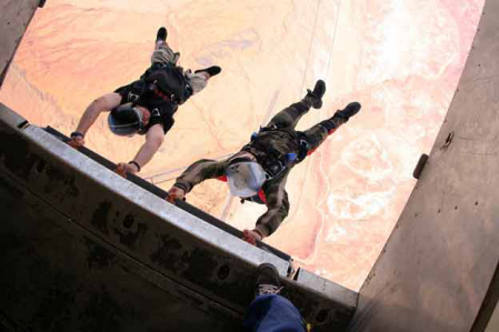 Two skydivers at Skydive Moab hang onto the plane outside the back door before jumping