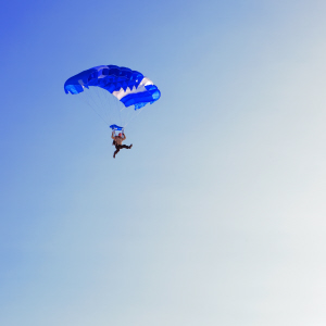 A jumper under a blue parachute canopy completing a BASE jump.