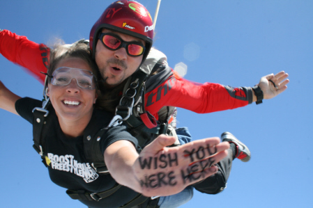 Skydive Taft Tandem skydivers: the student holds out her hand with the words, wish you were here, written with black ink