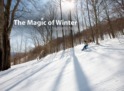 The magic of winter..happens here. A snowboarder boards down a mountain.