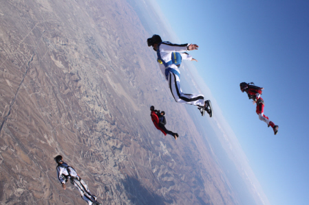 Four skydivers seamlessly fly through the air