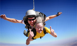 Skydiving granny at Skydive Moab gives two thumbs up during a tandem skydive