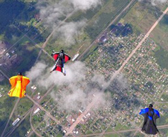 Three Skydive Superior Wingsuit Skydivers fly over a city
