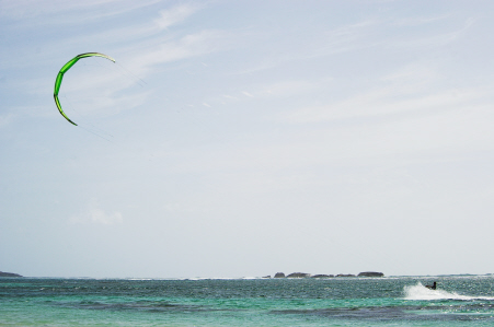 Kitesurfing: A kitesurfer uses a large green kite to surf across the crystal blue water.