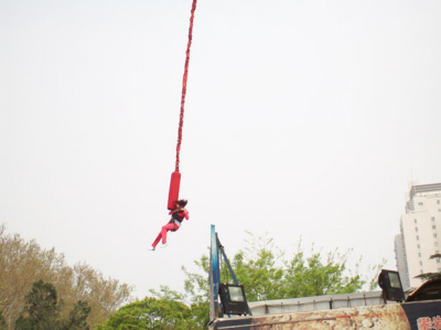 A bungee jumper in a full body harness stretches the bungee cord during a bungee jump from a bridge.