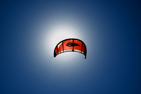 A red kitesurfing kite flies with the blue sky in the distance.