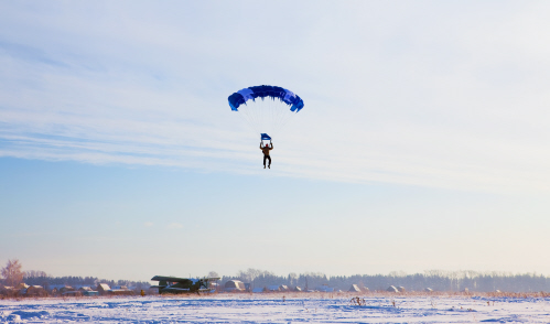 A skydiver with a blue canopy is about to land on a snow covered flat plain. A small plane sits in the distance.