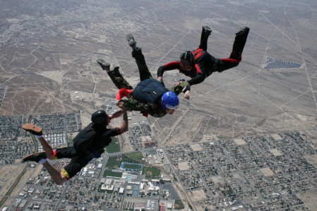 Two instructors stabalize an accelerated free fall student during a skydive