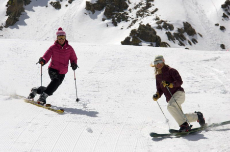 Two skiers ski down a mountain at Arapahoe Basin