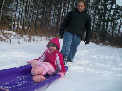 A man pushes a young girl down the hill on a sled at Porcupine Mountain