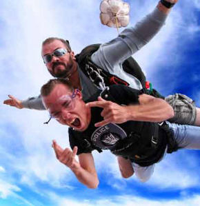 Skydive Moab - A closeup of a tandem skydive with blue skies and the student showing the rock sign