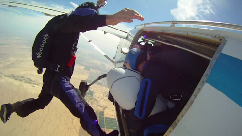 A skydiver jumps backward from the plane door to begin his skydive